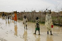 Wading across a flooded road in one of the IDP camps - the pools create ideal breeding ground for mosquitoes
